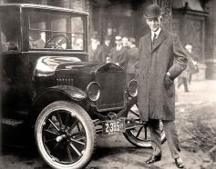 Henry Ford framför en av sina bilar.