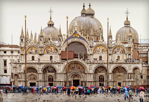Venice St. Mark's Square with St. Mark's Basilica in the rain, in front of it tourists with colorful umbrellas, Italy
