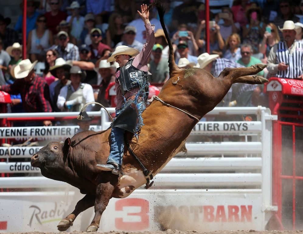 Edgar Durazo, of San Antonio, competes in the bull riding event during the first day of the Cheyenne Frontier Days Rodeo, Saturday, July 23, 2016, at Frontier Park Arena in Cheyenne, Wyo. (Blaine McCartney/Wyoming Tribune Eagle via AP)