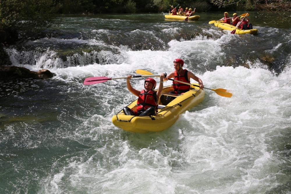 Två personer paddlar över en flod.